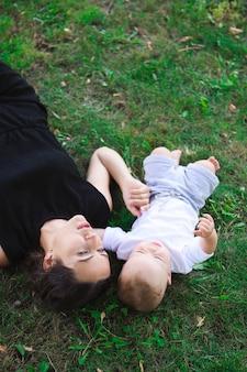 Милый веселый ребенок с матерью играть на открытом воздухе в парке