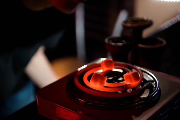 赤い熱い石炭とシーシャ水ギセル。リラックスしてシーシャの煙のためのココナッツ炭を使ったモダンな水ギセル。水ギセルと石炭から火花