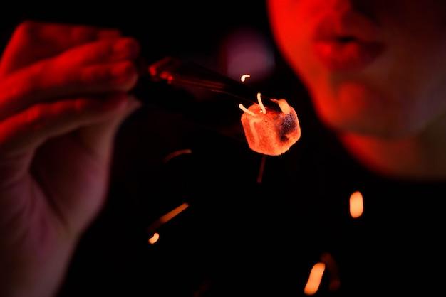 シーシャ水ギセル、赤熱石炭。男は火花飛ぶために石炭を吹きます。