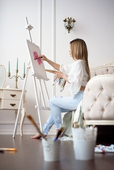 イーゼルを使用してアートスタジオで描く画家。白いキャンバス、サイドビュー肖像画に油絵の具で描く若い女性の肖像画
