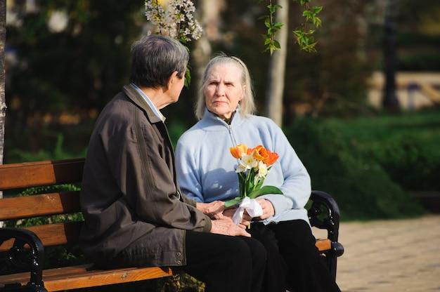 秋の公園に座って美しい幸せな老人