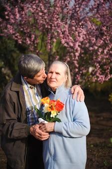Красивые счастливые старики сидят в осеннем парке
