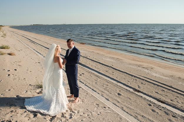 結婚式の日にビーチで愛のカップル。