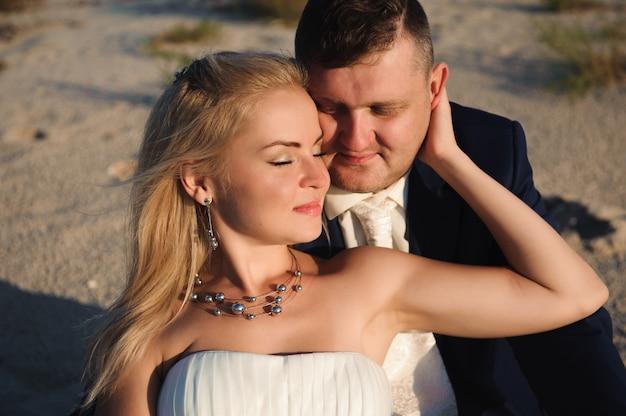 Жених и невеста у моря в день своей свадьбы.