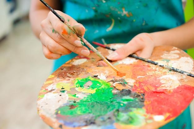 美しい少女は、アートレッスンに絵の具を描画します
