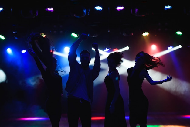 Молодые люди танцуют в клубе.