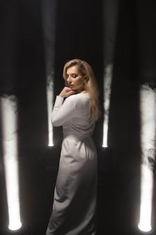 Роскошная блондинка плюс размер с белыми длинными волосами позирует в длинном белом платье на темной сцене в дыму при свете.