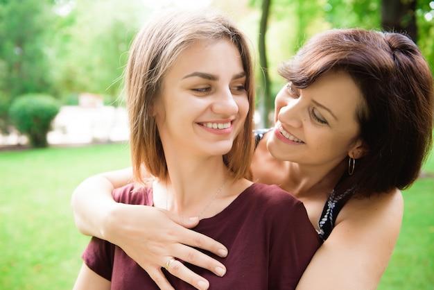 愛を込めて母親を抱きしめるかわいい若い娘。