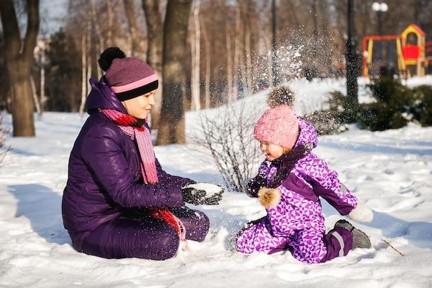 Мать и ее маленькая дочь, наслаждаясь прекрасный зимний день