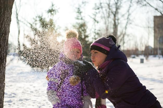 母と美しい冬の日を楽しんでいる彼女の小さな娘