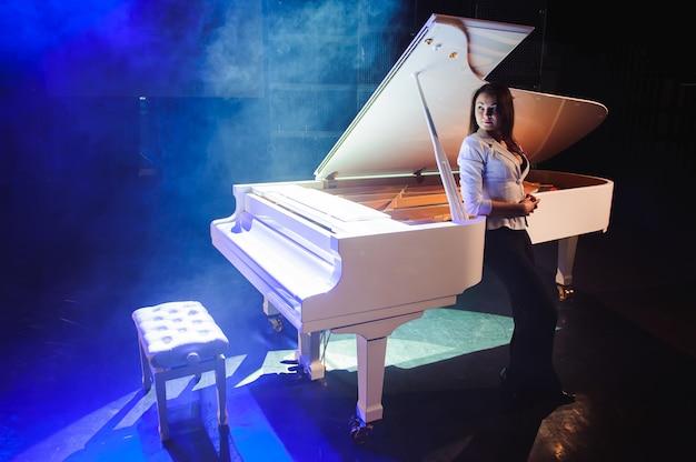 Красивая женщина возле белого пианино