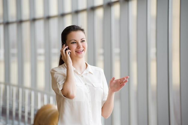 携帯電話で話している若いビジネス女性。