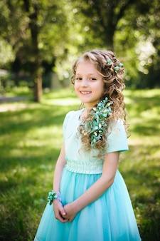 咲く春の庭でカメラを見て笑っている美しい少女