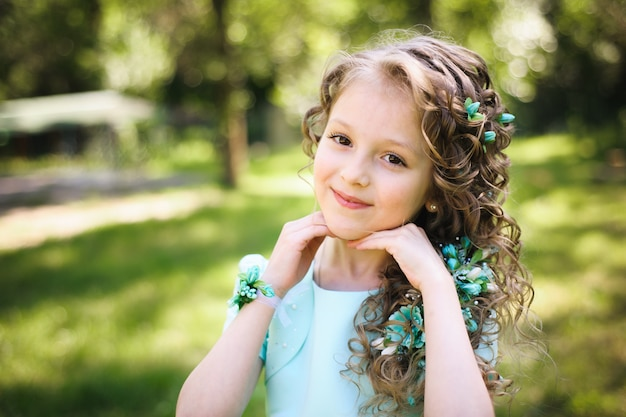 Красивая маленькая девочка улыбается, глядя на камеру в цветущем весеннем саду