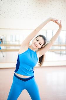 Женщина делает упражнения на растяжку на полу в тренажерном зале