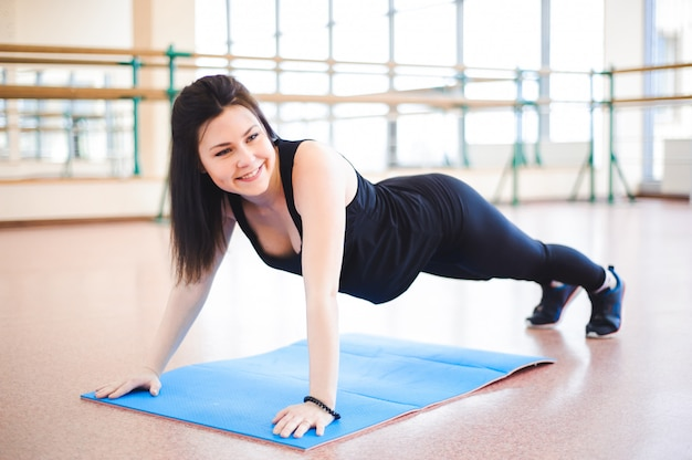 ジムで床にストレッチ体操をしている女性