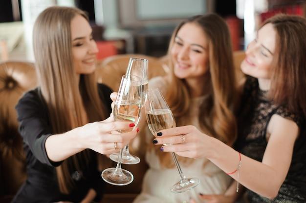 Веселые девушки звон бокалов шампанского на вечеринке.