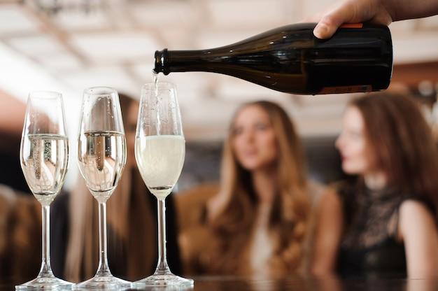 Мужчина наполняет бокалы шампанским для трех красивых молодых женщин