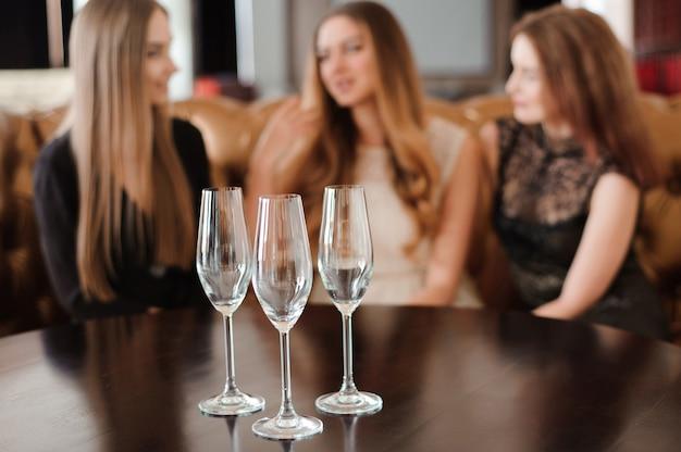 女の子の背景にシャンパンの空のグラス。