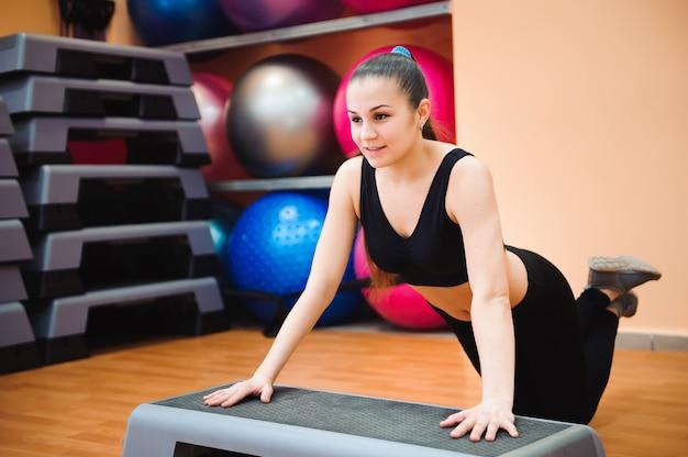 ステッパーで有酸素クラスを行う運動の女性トレーナー。スポーツ