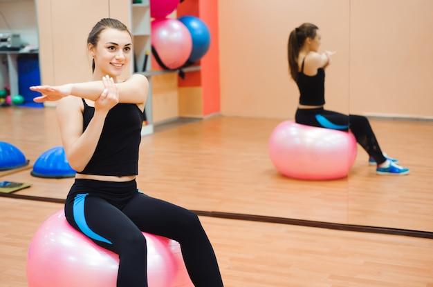 Счастливый милашка спортивная девушка, выполнять упражнения и улыбаться.