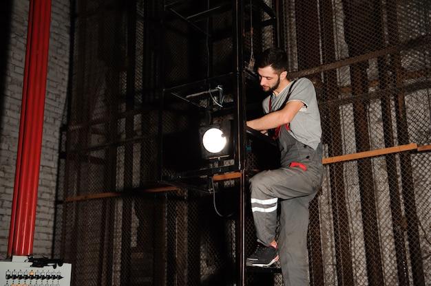 照明エンジニアがステージ上の照明を調整します。