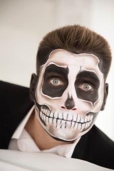 メイクアップハロウィーンを持つ男。吸血鬼、スケルトンを描く