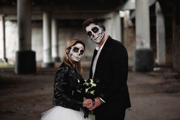 ハロウィーンのカップル。結婚式の服のロマンチックなゾンビに身を包んだ
