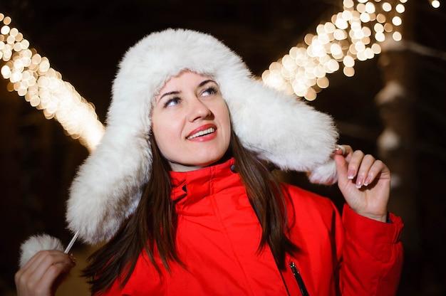 白いニットの毛皮の帽子を着ている若い美しい幸せな笑顔の女の子。通りでポーズをとるモデル。冬の休日の概念。