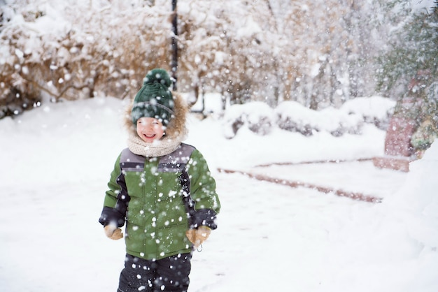 子供たちは最初の雪で公園を散歩します