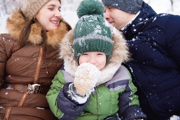 父と母は冬の森で幼い息子と一緒に歩きます。
