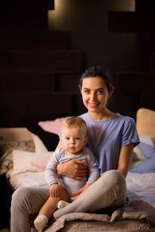 母と息子の子供の女の子が遊んで、ベッドでハグします。