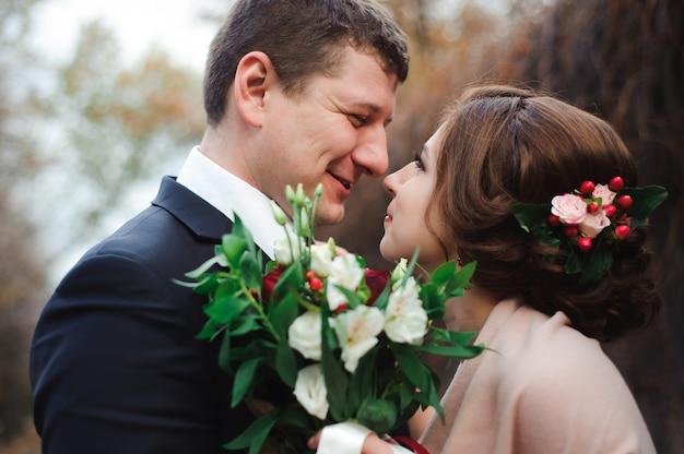 秋の自然の中で幸せな新婚夫婦の肖像画。