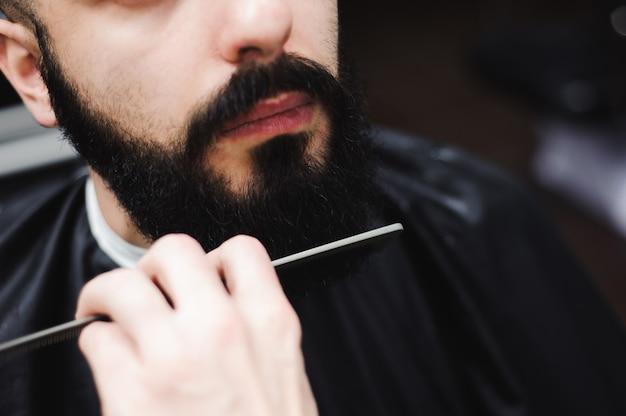 魅力的な男性の髪型を作る若いハンサムな理容室