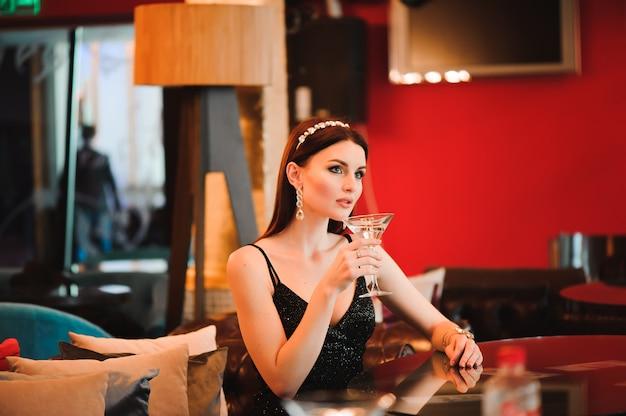 マティーニのグラスを保持している美しい女性の肖像画。