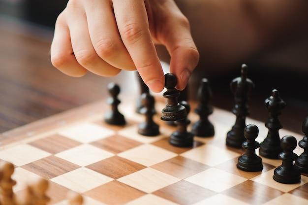 Рука движется шахматная фигура в конкурсе успеха игры.