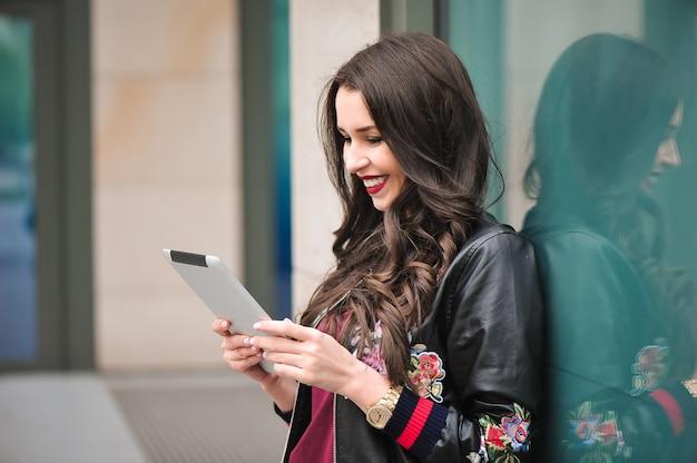 Молодая девушка с помощью планшета на улице, в стиле битник, на открытом воздухе