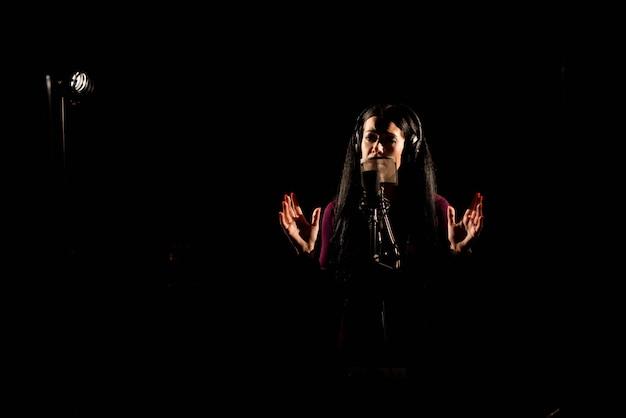 Женщина певец поет песню в студии звукозаписи.