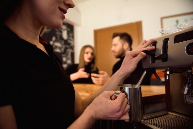 Профессиональная женская бариста держит металлический кувшин для разогрева молока с помощью кофемашины.