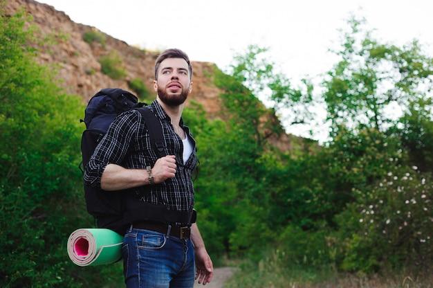 Путешественник молодого человека с ослаблять рюкзака напольный.