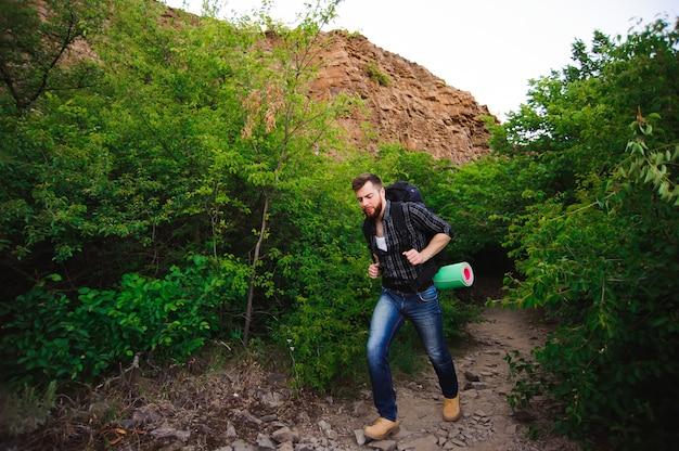 Человек путешественника идя с рюкзаком в скалистых горах.