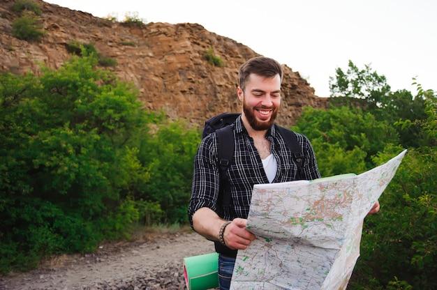 Крупным планом молодого человека, как он читает карту, путешествуя в одиночку