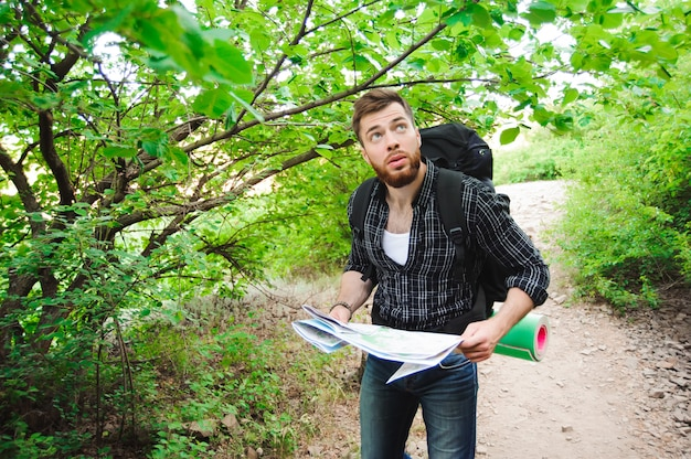 Молодой человек путешественник с картой рюкзак отдыха на открытом воздухе