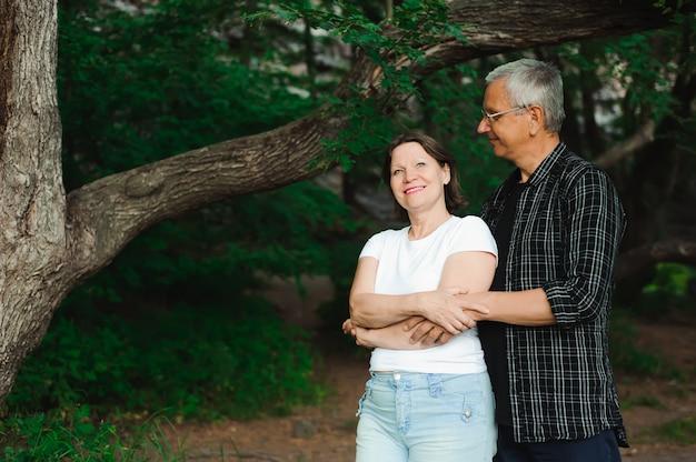 年配のカップルが一緒に森を歩いてクローズアップ。
