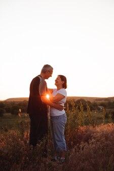ロマンスと太陽を楽しんで日没で手を繋いでいるカップル。