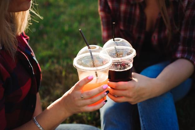 公園の緑の草にジュースを飲む友人