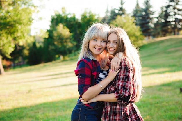 Две подруги смеются и обнимаются. обними и улыбнись