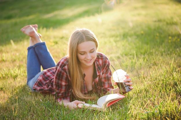 公園、女性、緑で本を読んでいる女の子。