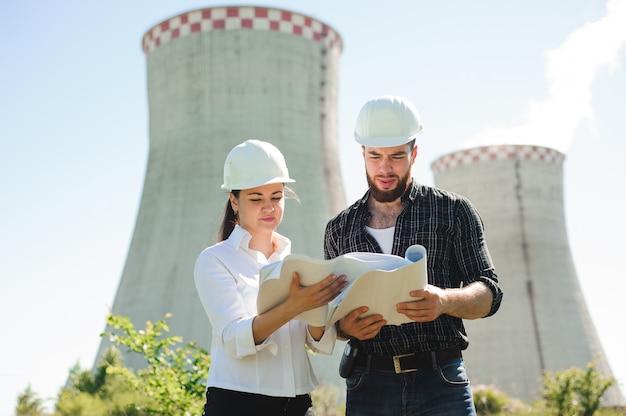 Два инженера стоят на электростанции, обсуждают план.