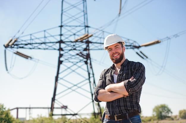 送電線の下に白いヘルメットを持つエンジニア。エンジニアの仕事